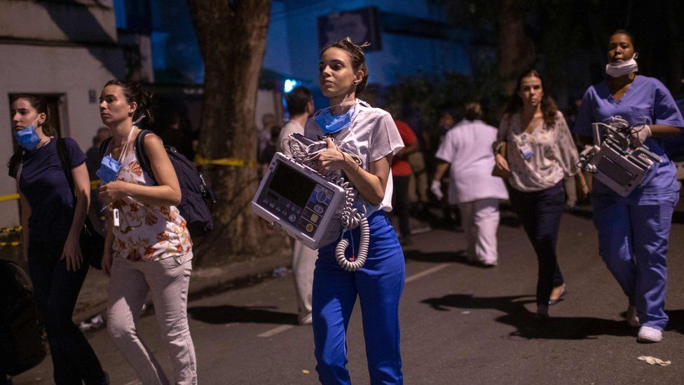 Employees are seen after a fire hit the Badim Hospital in Rio de Janeiro, Brazil September 12, 2019