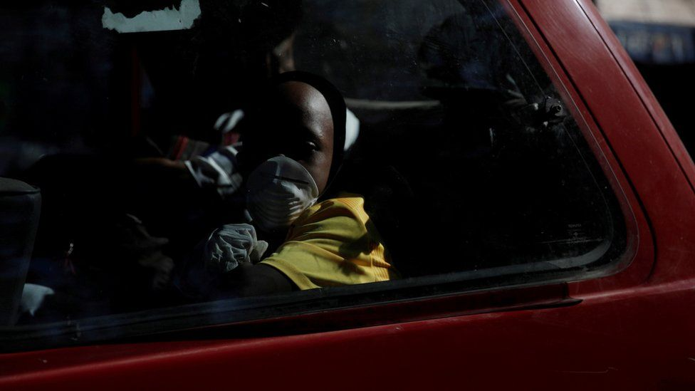"""A boy wearing protective gloves and a mask travels in a van, after Haiti""""s government declared a state of emergency"""