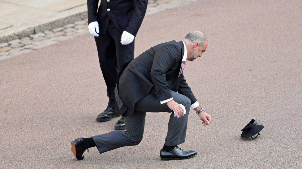 A guest chases after a hat in the wind as he arrives for the wedding of Princess Eugenie to Jack Brooksbank