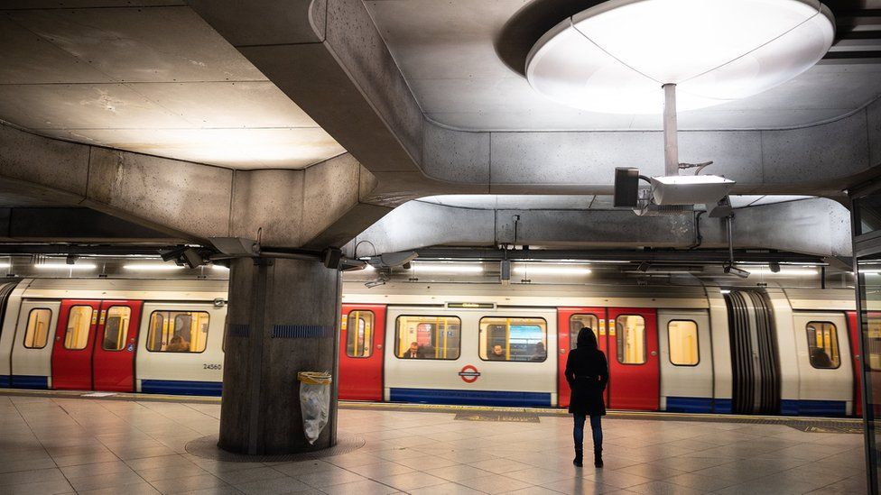 Woman stands at empty Tube station