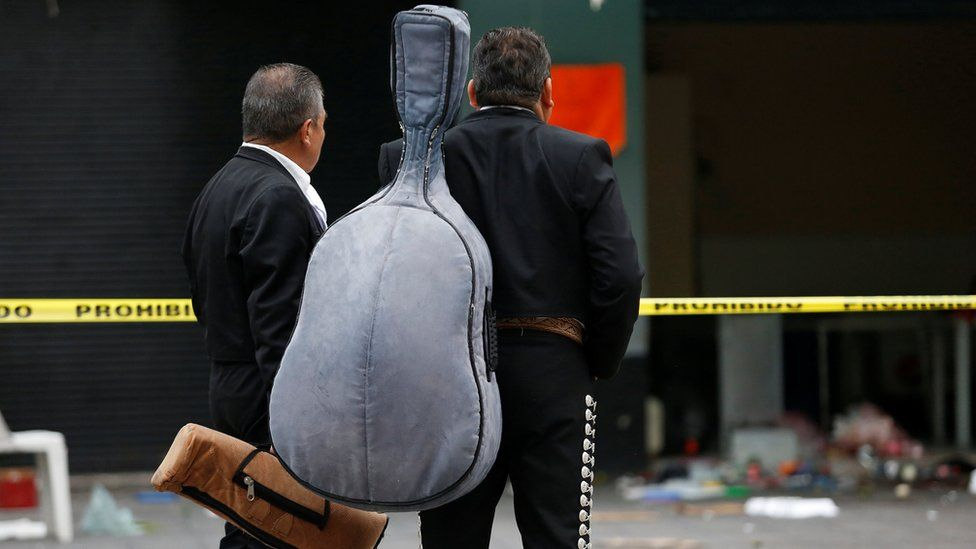 Mariachi musicians observe a crime scene hours after unknown assailants attacked people with rifles and pistols at an intersection on the edge of the tourist Plaza Garibaldi in Mexico City, Mexico September 15, 2018
