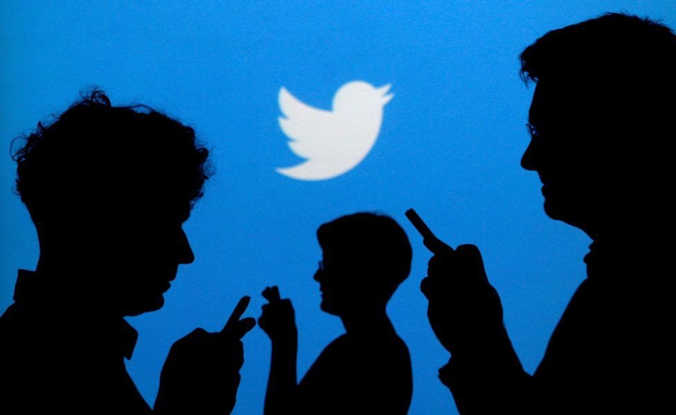 People holding mobile phones silhouetted against a backdrop of the Twitter logo