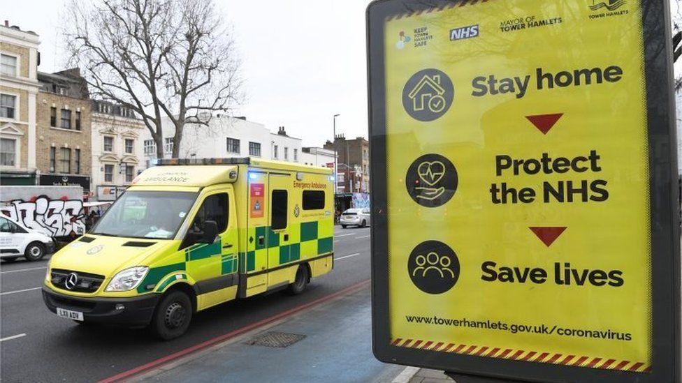 An ambulance passes a coronavirus poster in east London