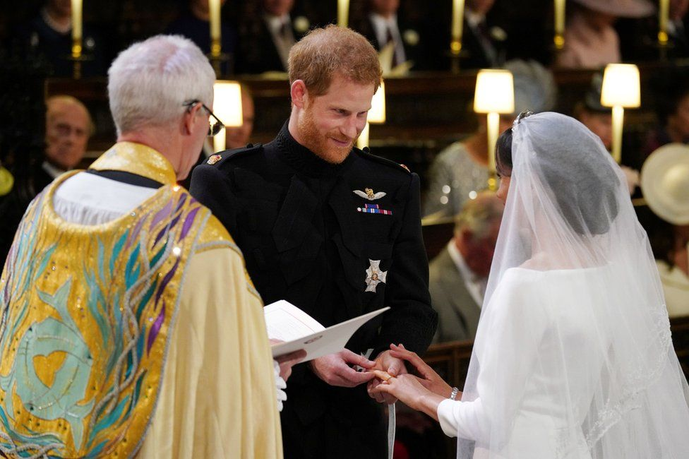 "Prince Harry places the wedding ring on the finger of Meghan Markle in St George""s Chapel"