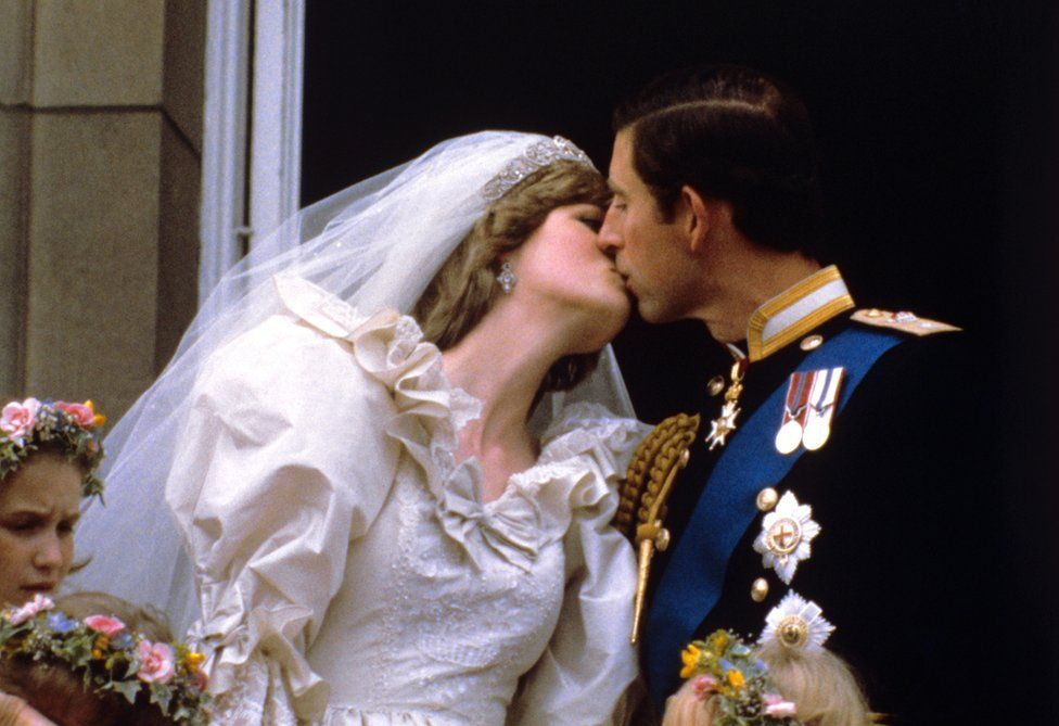 The newly married Prince and Princess of Wales kiss on the balcony of Buckingham Palace after their wedding ceremony at St. Paul's cathedral.