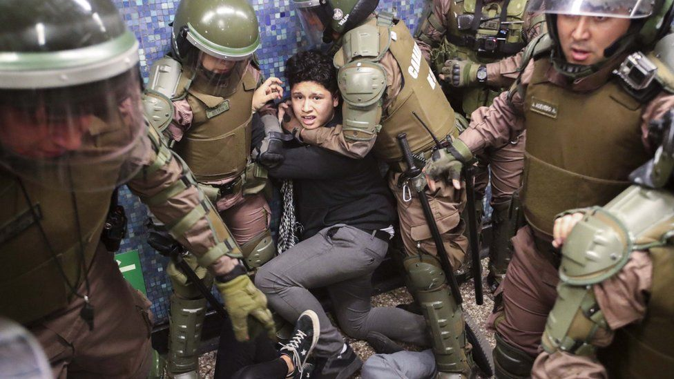 Chilean police detain a protester at the Los Heroes metro station in the middle of a demonstration in Santiago