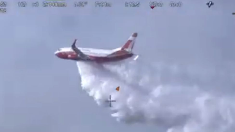 The Coulson Aviation 737 Fireliner Airtanker drops water over a bushfire in New South Wales