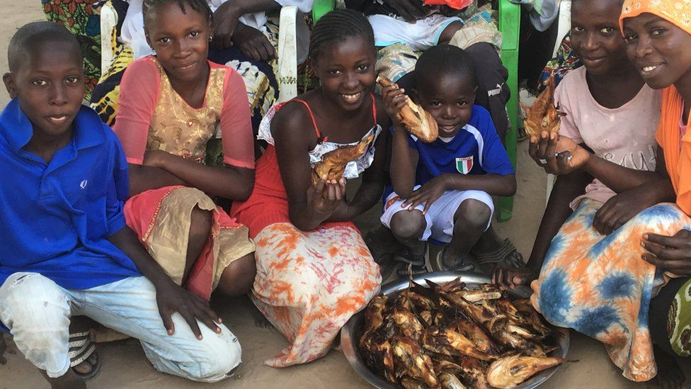 "Young members of ""Taka"" Babucarr Bojang's family posing around a plate of fish"