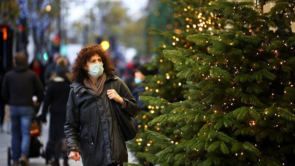 Woman in mask next to Christmas tree