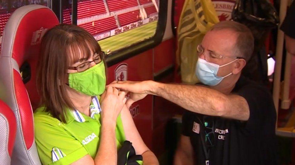 Woman in Asda uniform gets vaccination