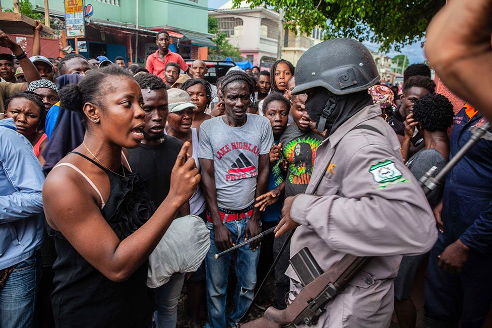 A woman argues with a military guard as Haitians stand in line to receive a bag of food as part of the humanitarian aid provided by FAES (Fund for Economic and Social Assistance) on 16 August 2021 in Les Cayes, Haiti