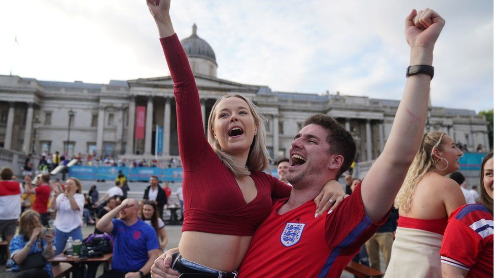 """Fans in Trafalgar Square, London, celebrate Harry Kane""""s first goal as they watch the Euro2020 quarter final match between England and the Ukraine."""