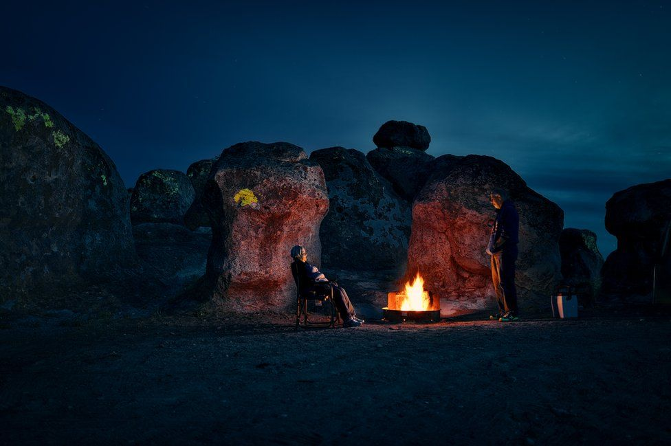 A couple sit in the darkness illuminated by a small camp fire