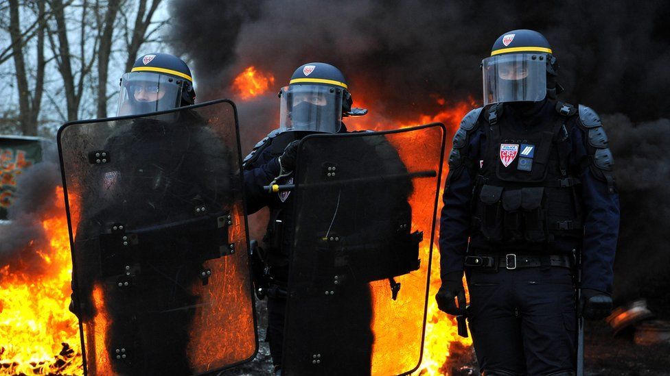 Riot police stand near a fire during a demonstration against rising fuel and oil prices in Crespin, northern France