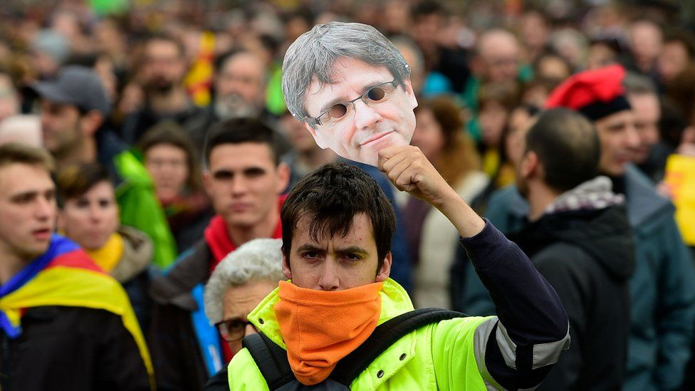A protester holds a mask of Catalonia's former president Carles Puigdemont during a demonstration in Barcelona on 25 March 2018