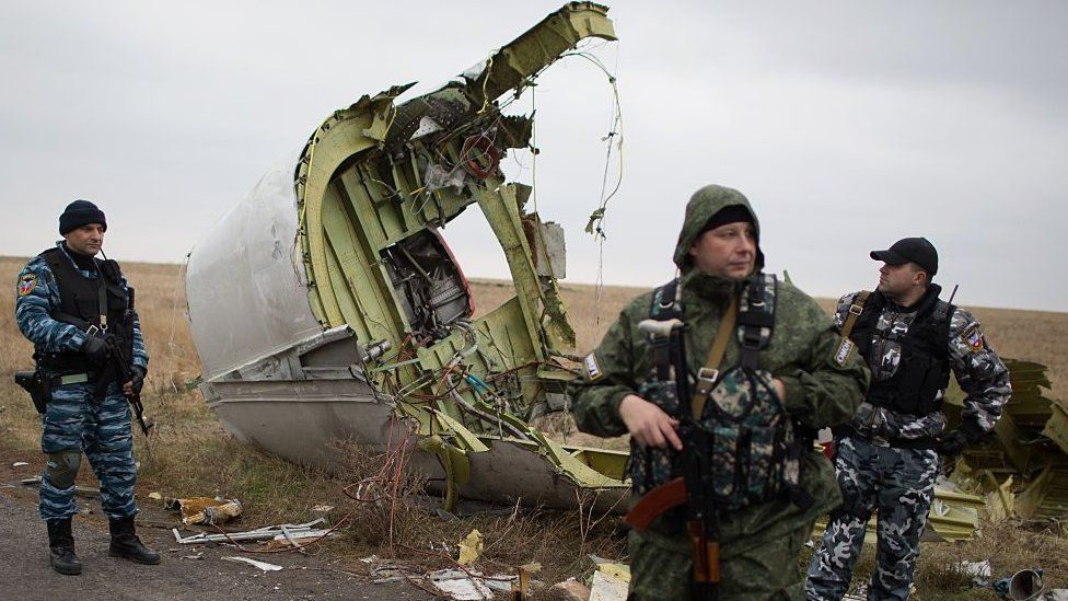 Pro-Russian gunmen stand guard as Dutch investigators (unseen) arrive near parts of the Malaysia Airlines Flight MH17 at the crash site near the Grabove village in eastern Ukraine on November 11, 2014