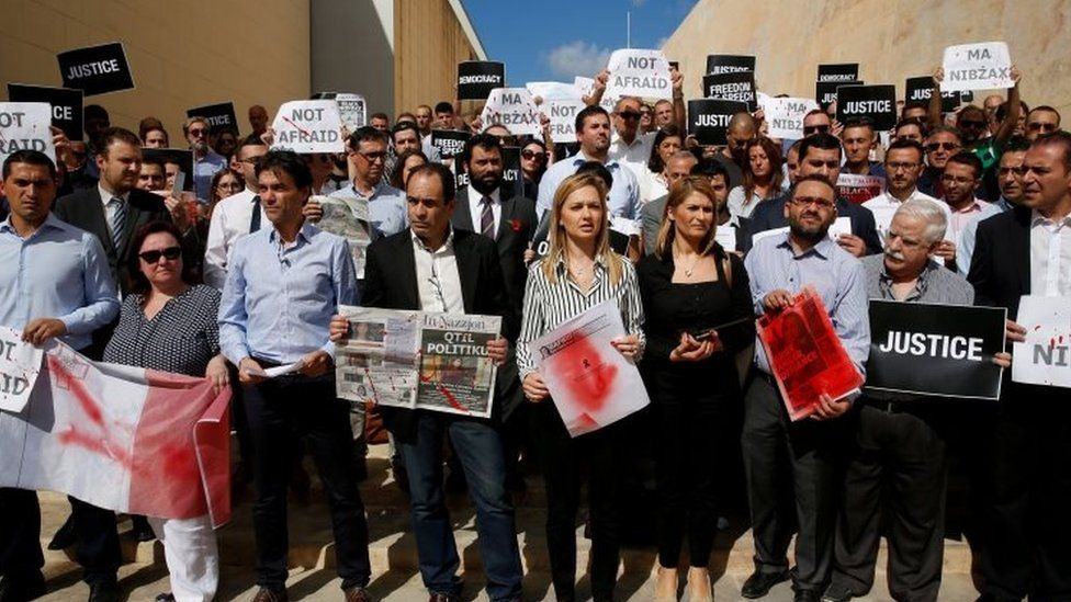 Journalists hold front pages and placards splattered in blood-red paint in Valletta, Malta. Photo: 19 October 2017