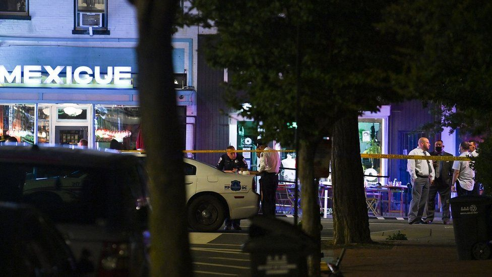 Police officers stand outside a restaurant after a shooting in Washington, DC, on July 22, 2021