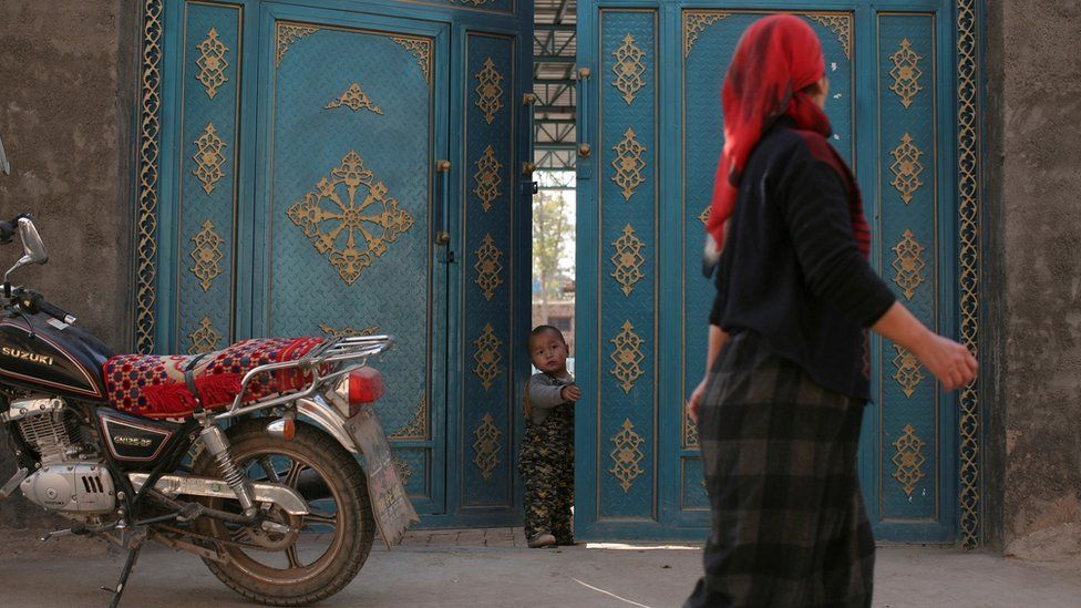 Woman walks past door with small child peeking out, Xinjiang (file pic)