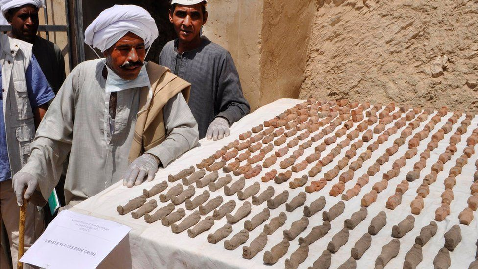 Two men next to a table covered in rows of clay humanoid figurines