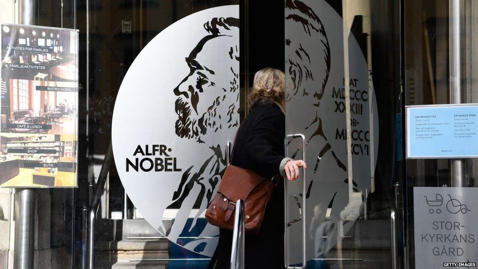 A woman opens the door of the Alfred Nobel Museum in Stockholm, Sweden, that is located in the building where will be announced the winner of the 2017 Nobel Prize in Literature on October 5, 2017.