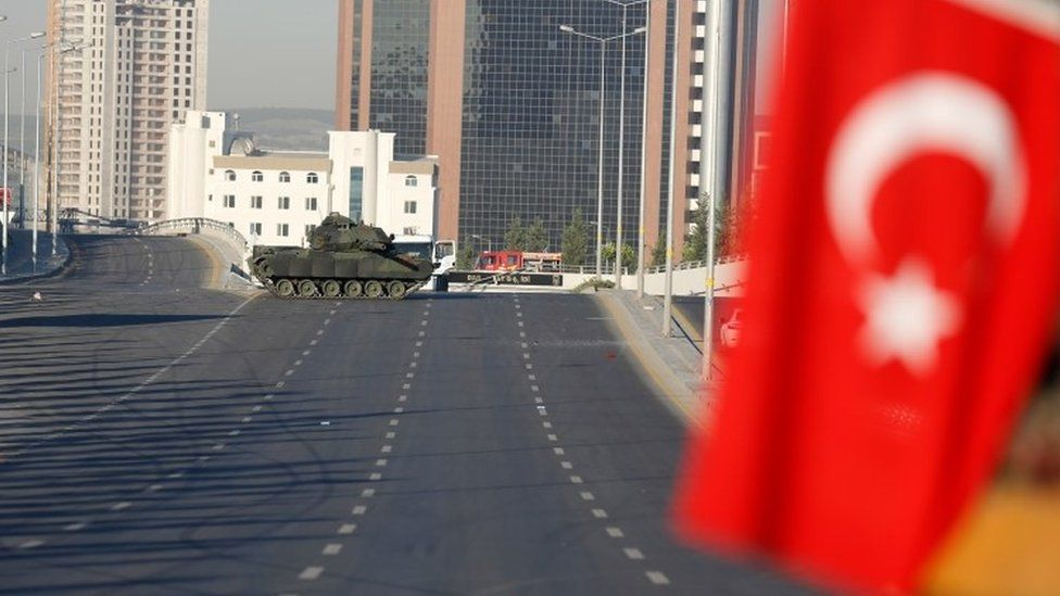 An abandoned tank is seen near a Turkish flag