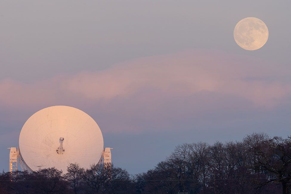 An image by Jodrell Bank showing the Lovell Telescope with the moon in the sky