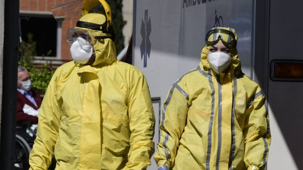 Healthcare workers wearing protective suits stand at the entrance of the Severo Ochoa Hospital in Leganes, near Madrid, on April 03, 2020