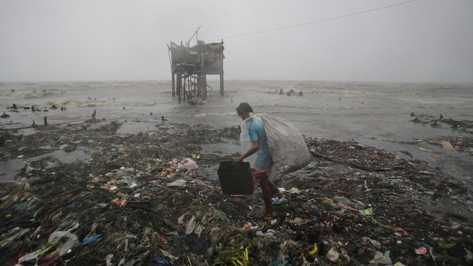 A Filipino man scavenges recyclable materials by the sea as strong winds and rains caused by the typhoon hit the coastal town of Navotas, north of Manila