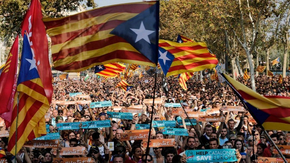 Pro-independence supporters wave flags outside the Catalan regional parliament
