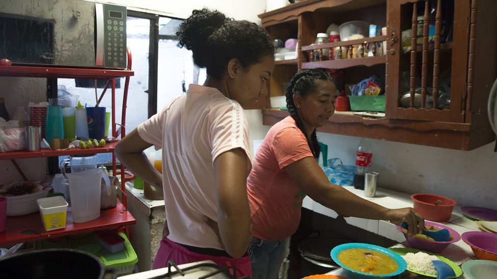 Cousuelo Villega Mendoza, 44, and her daughter cook the Colombian stew Mondongo to serve at a restaurant they run out of the home Villega built