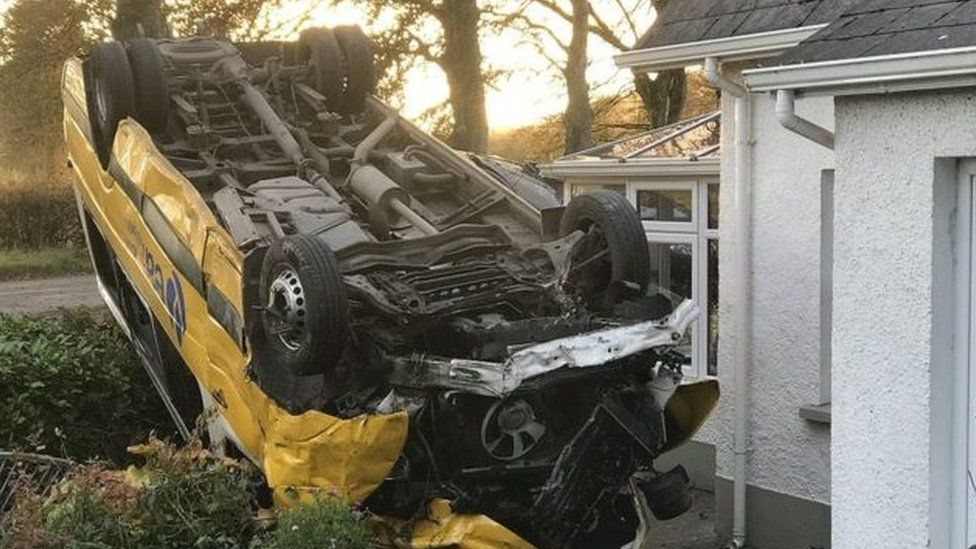 The bus came to rest on its roof next to a house, after colliding with a car at a crossroads near Augher