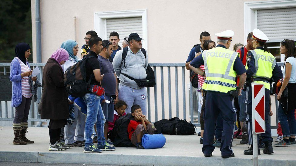 Migrants walking from Slovenia speak to police officers as they arrive to the border town of Bad Radkersburg, Austria, on 20 September.