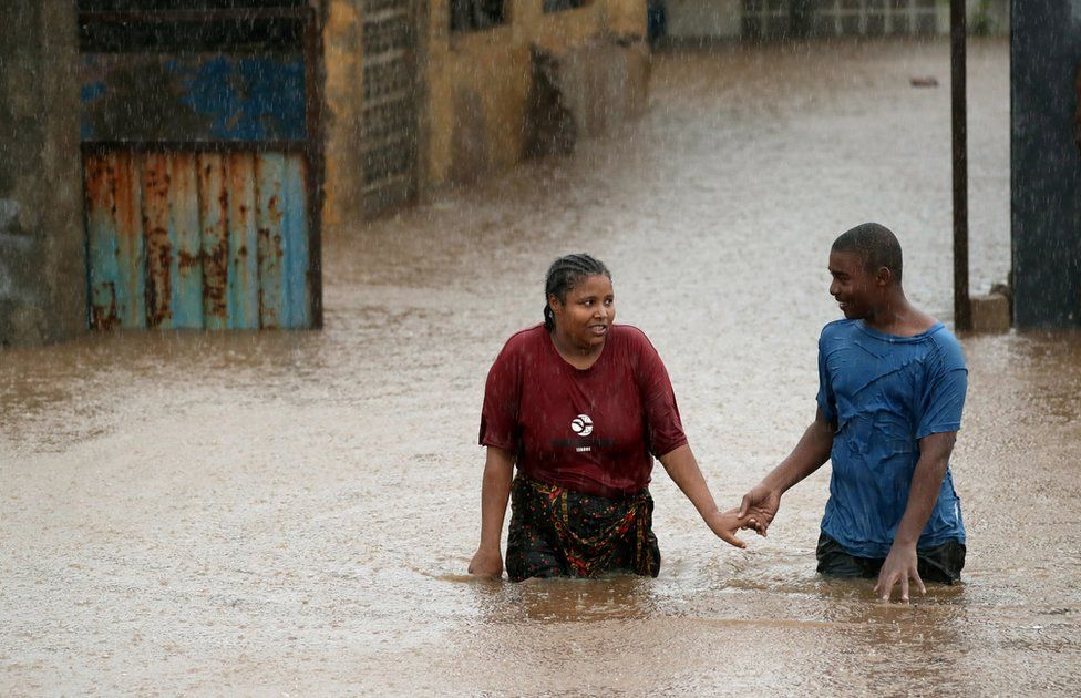 A man helps a woman through a flooded neighbourhood in the aftermath of Cyclone Kenneth, in Pemba, Mozambique