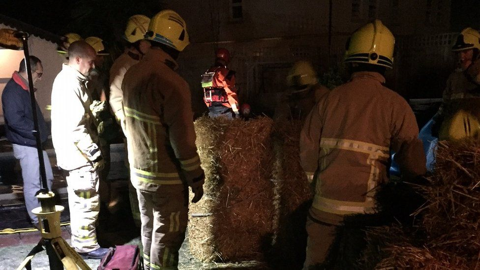 Fire fighters surrounded by hay bales