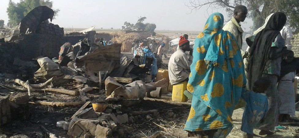 People walk at the site after a bombing attack of an internally displaced persons camp in Rann, Nigeria January 17, 2017.