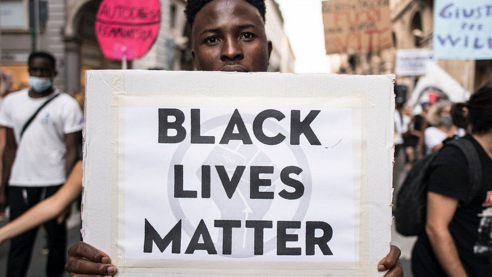 """Man with a banner reading """"Black Lives Matter"""" during a protest against racism by the Black Lives Matter movement on September 13, 2020 in Turin, Italy"""