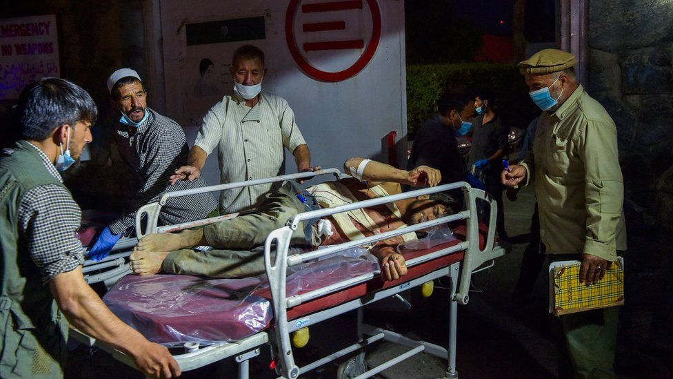 Hospital staff bring an injured man for treatment after the Kabul airport attack
