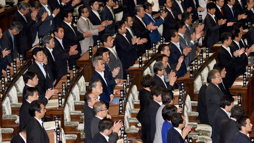 Members of Japan's lower house of parliament stand up to support a bill during the plenary session in Tokyo on June 2, 2017.