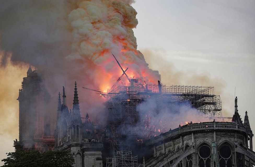 The spire collapses while flames are burning the roof of the Notre-Dame Cathedral