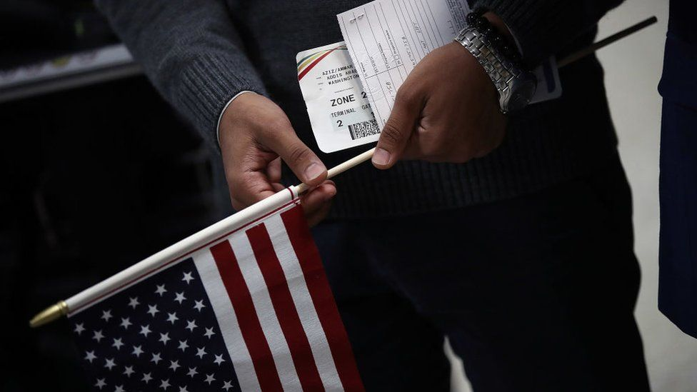 A man holds travel documents after arriving from Yemen at Dulles International airport in Washington, DC.