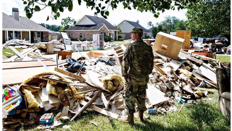 """Chris Daves, a National Guardsman, surveys the damage from a friend's yard. He's there to help and listen, """"We're fellow Army men, that's what we do."""" Watson, LA."""