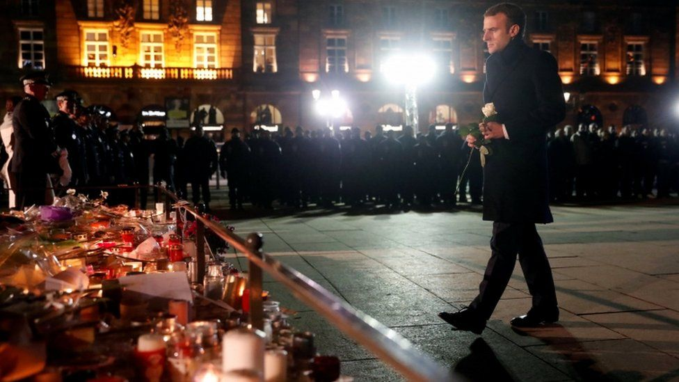 The French president lays a flower at a monument for the victims in Strasbourg