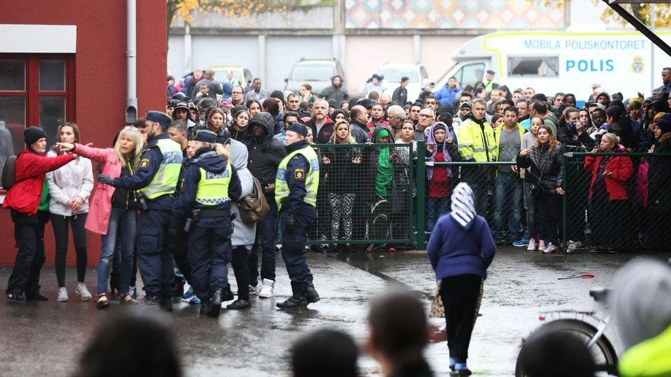 Swedish police officers give information to people as they secured the area outside a primary and middle school in Trollhattan, southwestern Sweden (October 22, 2015,