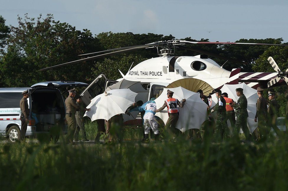 Police and military personnel use umbrellas to cover around a stretcher near a helicopter and an ambulance at a military airport in Chiang Rai