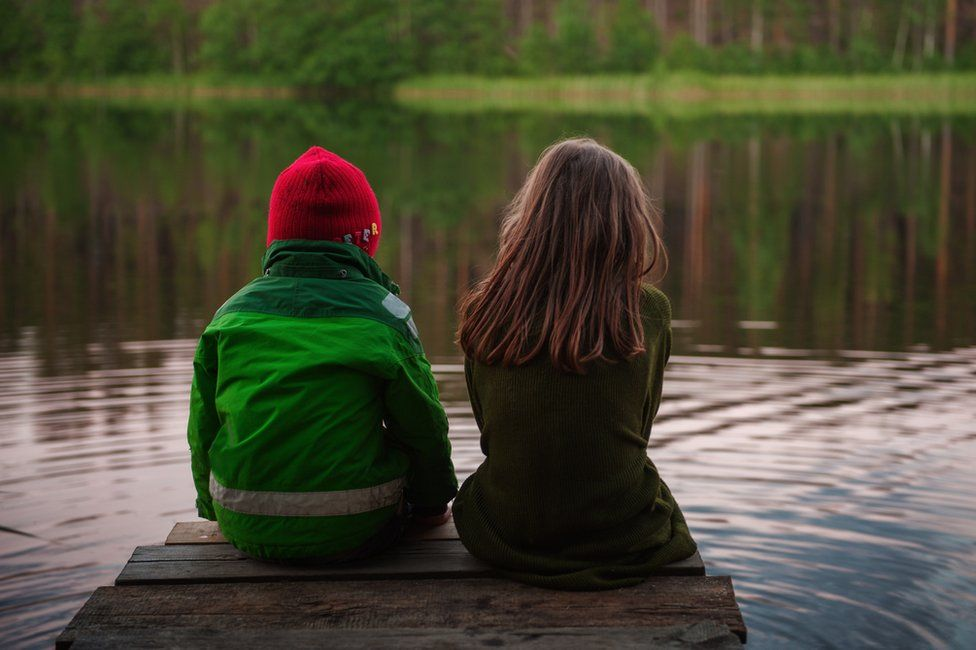 A boy and girl sit on a pier