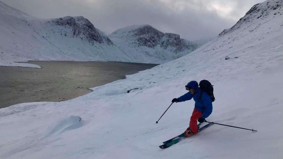 Skier on slope next to loch