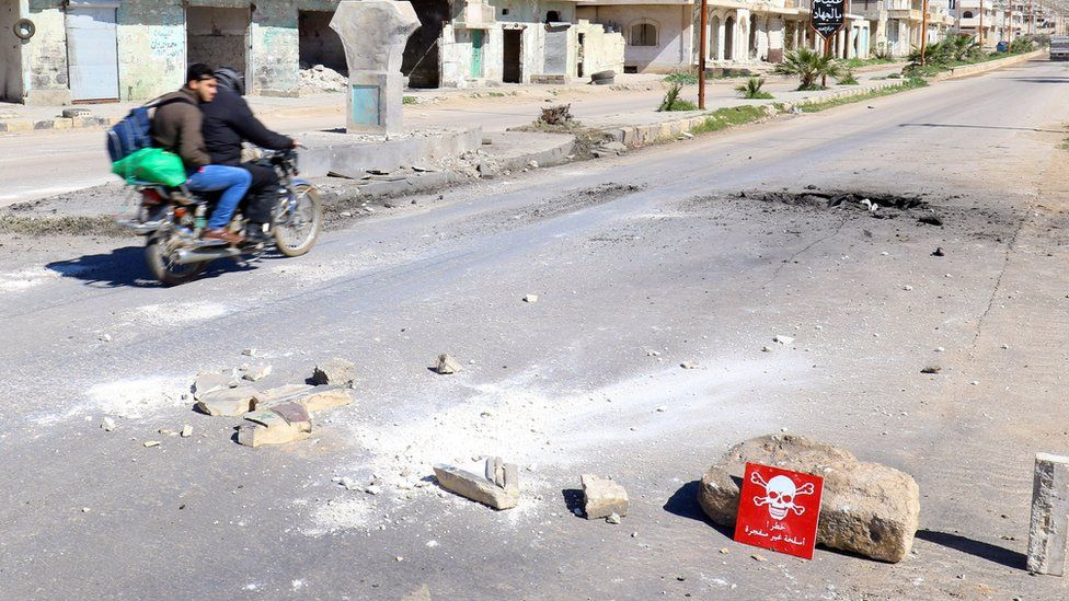 Men ride a motorbike past a hazard sign at a site hit in an alleged chemical weapons attack in Khan Sheikhoun, Syria (5 April 2017)