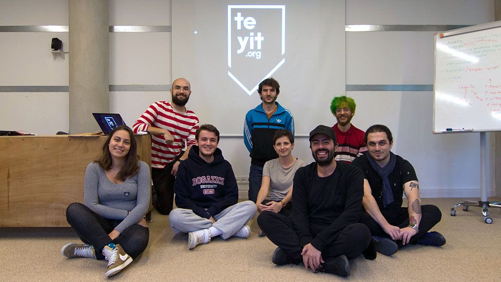 Eight members of the Teyit team sit in their office in front of their logo, smiling together