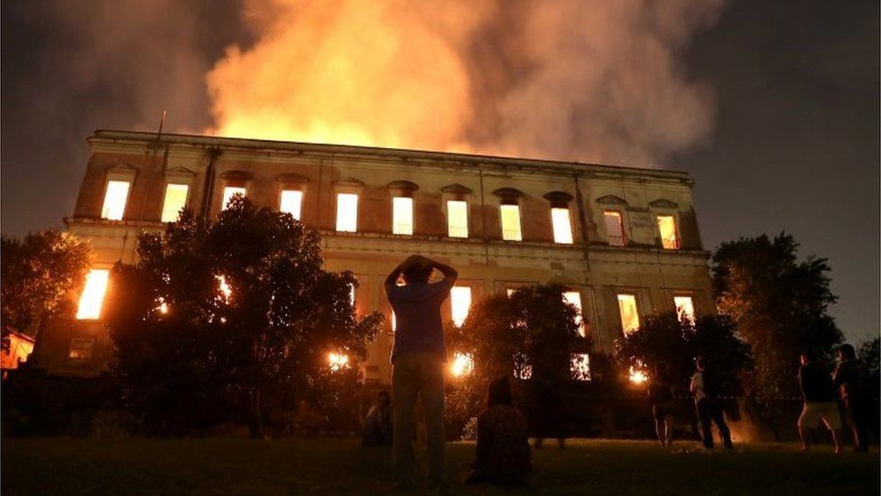 People watch as a fire burns at the National Museum of Brazil in Rio de Janeiro, .